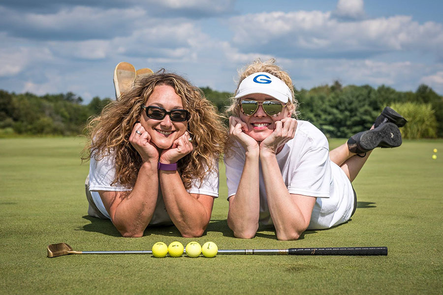 2 women lying on green with golf clubs
